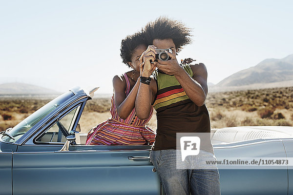 A young couple  man and woman by a pale blue convertible on the open road  holding a camera.