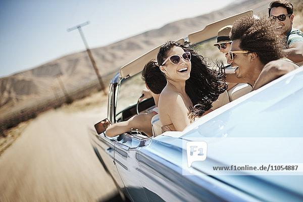 Eine Gruppe von Freunden in einem hellblauen Cabriolet auf offener Straße  die über eine trockene  flache  von Bergen umgebene Ebene fahren.
