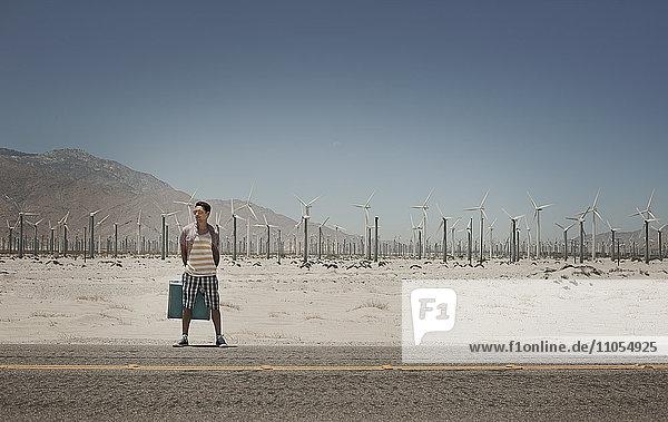 Ein Mann steht mit einem Koffer am Rande einer Autobahn  mit Windturbinen im Hintergrund.