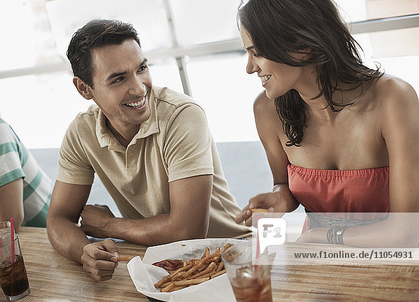 A young couple sitting together sharing a bowl of french fries in a diner.