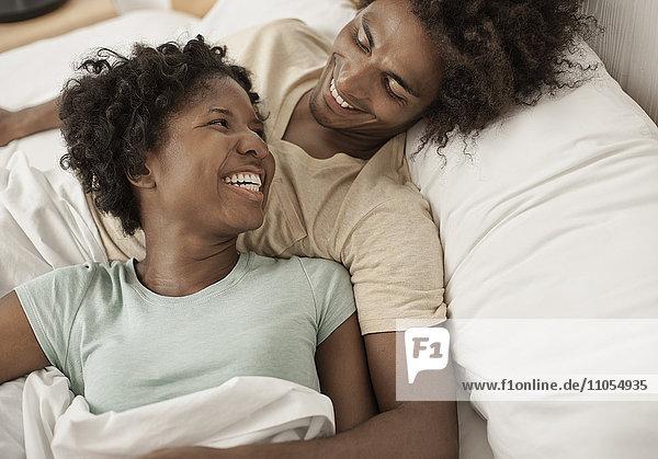 Ein junges Paar  das sich hinlegt und sich gegenseitig anstarrt  die Arme umeinander gelegt.