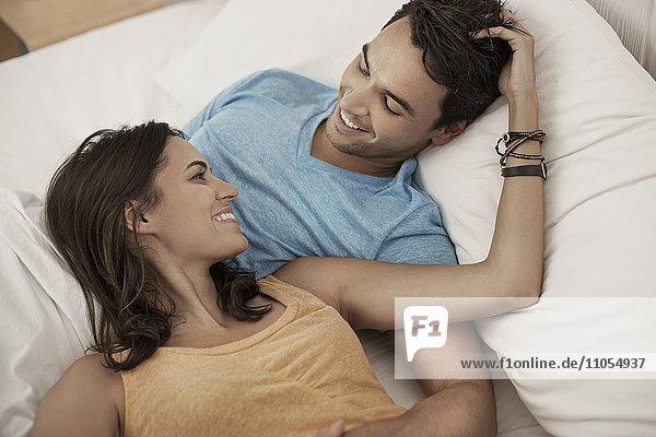 Ein junges Paar liegt auf einem Sofa und starrt sich an  ein Mann und eine Frau  ein Freund und eine Freundin.