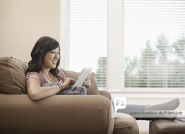 A woman seated on a sofa by a window using a digital tablet.