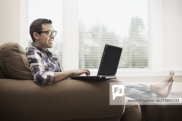 A man seated on a sofa  using a laptop computer.