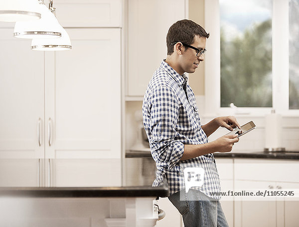 A man sitting at home using a digital tablet.