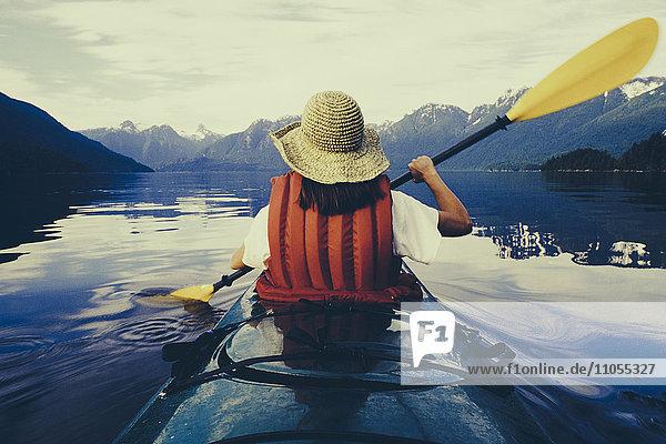 Eine Seekajakfahrerin auf dem flachen  ruhigen Wasser des Muir Inlet im Glacier Bay National Park.