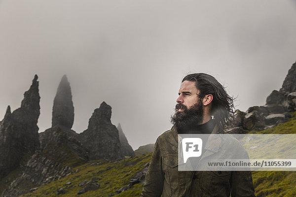 Ein Mann steht mit einer Kulisse aus Felsspitzen auf der Skyline  einer dramatischen windgepeitschten Landschaft und niedrigen Wolken.