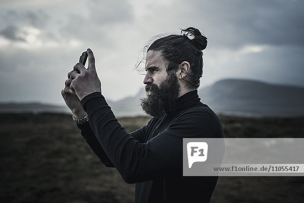 Ein Mann  der mit einem Smartphone fotografiert.