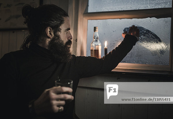 A man sitting alone in a room with a bottle of whisky and a glass  wiping condensation off the window to see outside. A lit candle.