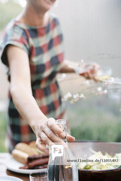 Eine Frau  die zwei Gläser hält und nach einer Flasche Wein greift.