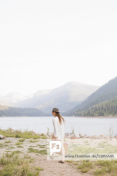 Eine Frau mit Hut und weißem Hemd mit einem Korb  am Ufer eines Bergsees.