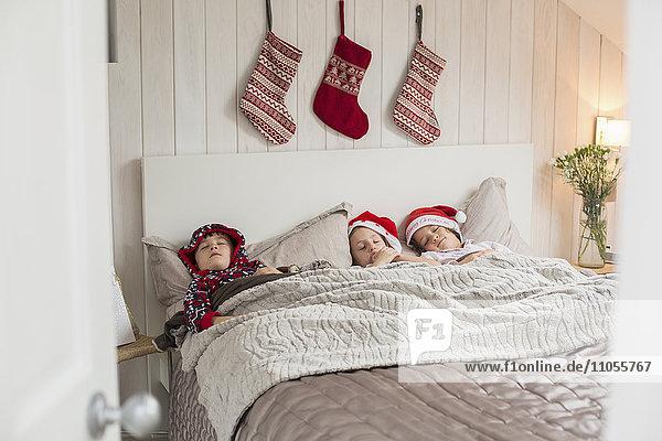 Drei Kinder in einem Doppelbett  über deren Köpfen Weihnachtsstrümpfe an der Wand hängen.