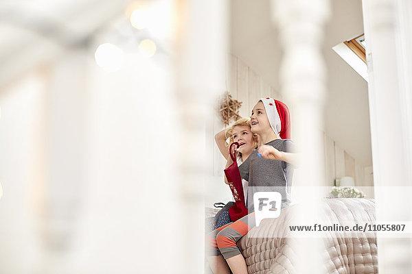 Zwei Kinder,  ein Junge und ein Mädchen,  die durch eine Schlafzimmertür gesehen werden,  schauen aufgeregt auf und wachen am Weihnachtsmorgen auf.