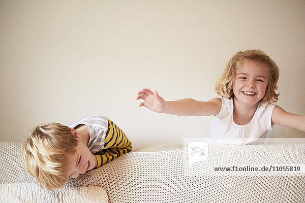 Zwei Kinder spielen hinter einem Sofa  ein Junge und ein Mädchen lachen.
