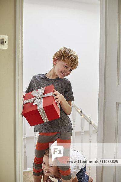 Weihnachtsmorgen in einem Familienhaus. Zwei Kinder auf der Treppe mit Geschenken.