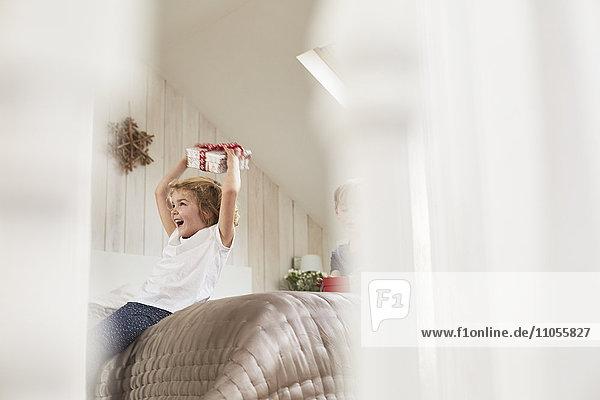 Weihnachtsmorgen in einem Familienhaus. Ein Mädchen hält ein Geschenk über ihrem Kopf.