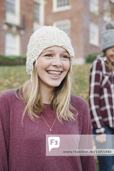 Two girls outdoors in woolly hats in autumn.