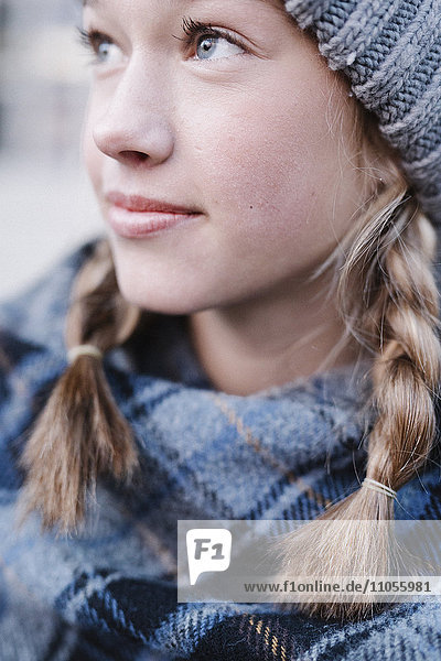 A teenage girl in a tartan plaid shawl and woolly hat outdoors in the winter.