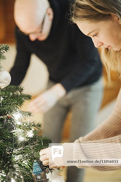 Ein Vater und eine Tochter schmücken einen Weihnachtsbaum.