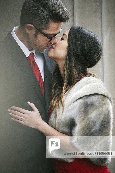 Ein Paar in Abendgarderobe  ein Mann und eine Frau  die sich in einer Stadt auf der Straße küssen.
