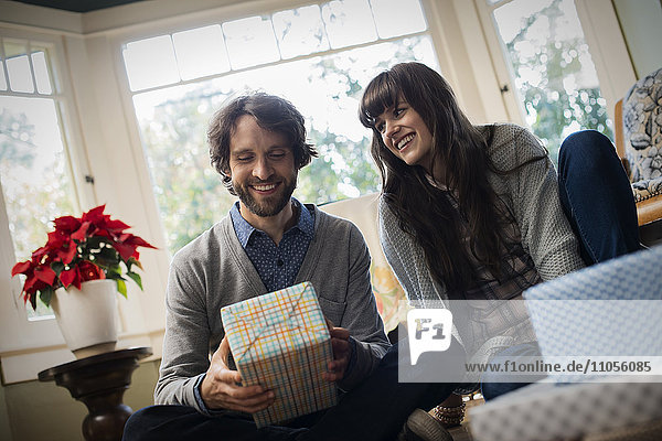 A couple on a sofa  exchanging wrapped presents.