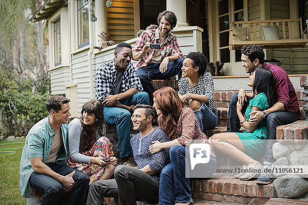 A group of friends sitting on the steps of a house porch  talking and laughing.
