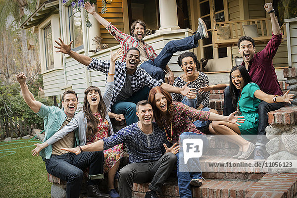 A group of friends sitting on the steps of a house porch  posing and laughing  arms outstretched.