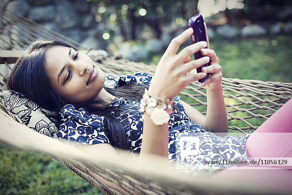 A woman lying in a garden hammock taking selfies with her phone.