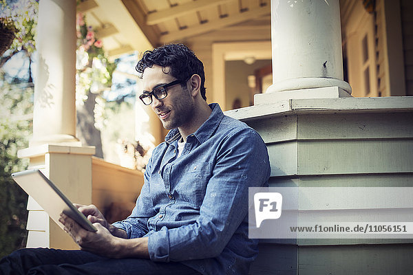 A man sitting relaxing in a quiet corner of a porch  using a digital tablet.