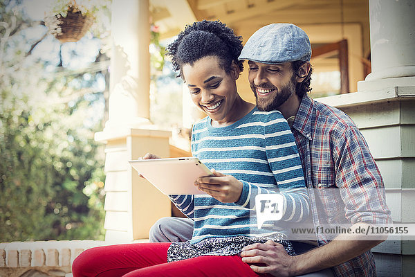 A couple  a man and woman seated on the porch steps  laughing  sharing a digital tablet.