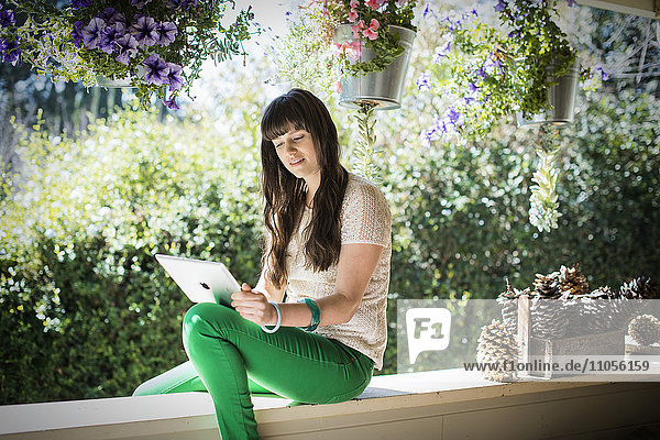 A woman seated on a shady porch using a laptop  surrounded by flowering plants.