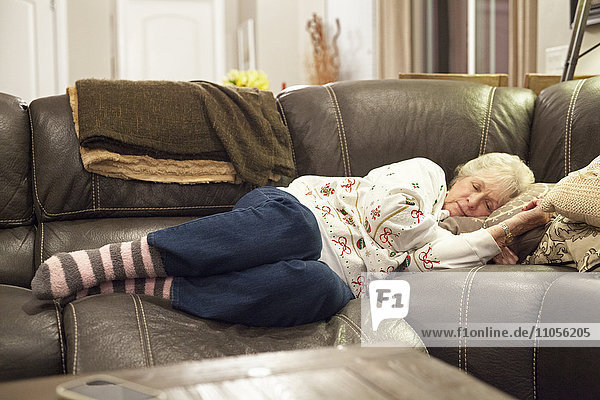 A grey haired woman lying on a sofa taking a nap.