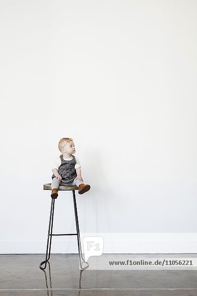 A young child  a baby girl sitting on a tall stool.