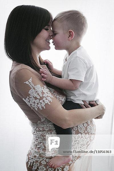 Eine schwangere Frau hält ihren kleinen Sohn im Arm.