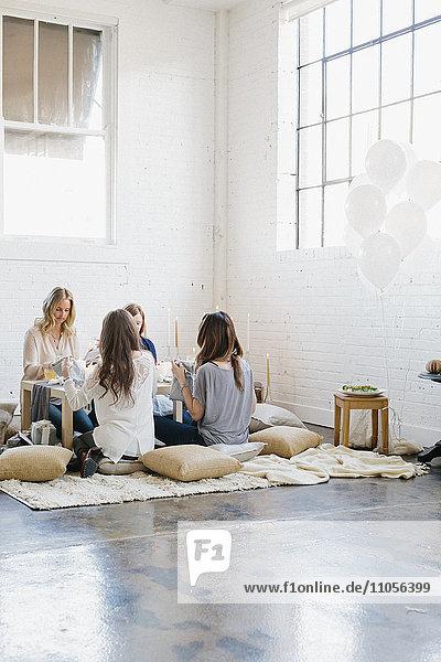 Vier Frauen saßen an einem niedrigen Tisch auf Kissen.