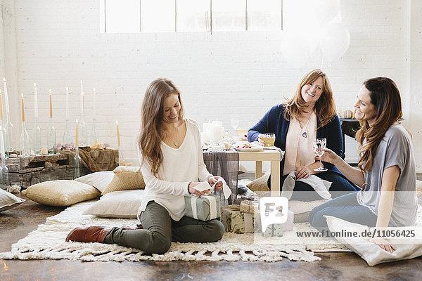 Drei Frauen bei einer Feier  eine öffnet einen Stapel Geschenke.