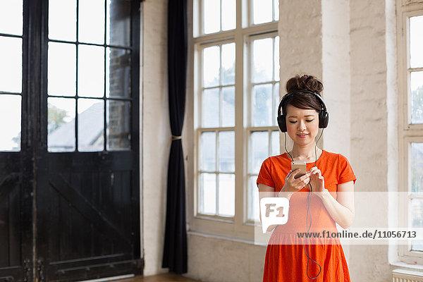 Junge Frau mit Kopfhörern  die in einem Probestudio steht und Musik hört.