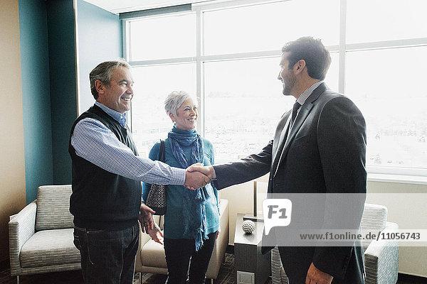 Ein Mann  der ein reifes Paar in einem Büro begrüßt.