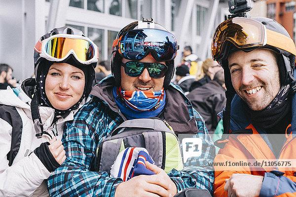 Drei Personen  eine junge Frau und zwei Männer in Skiausrüstung  in einer Reihe auf Skiurlaub.