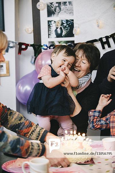Eine Familie versammelte sich  um den Geburtstag eines einjährigen Mädchens zu feiern. Ein Kuchen mit vielen Kerzen.