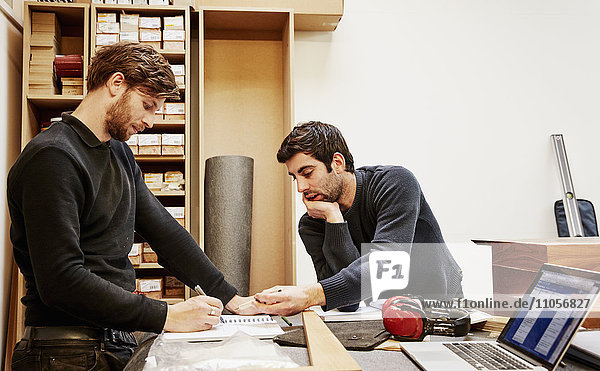 Eine Möbelwerkstatt  die maßgeschneiderte zeitgenössische Möbelstücke unter Verwendung traditioneller Fertigkeiten im modernen Design herstellt. Zwei Personen diskutieren über einen Entwurf und beziehen sich dabei auf Zeichnungen und Laptop-Computer.