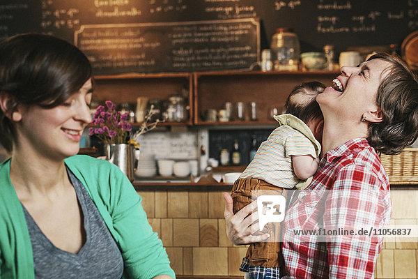 Zwei Frauen  ein gleichgeschlechtliches Paar mit ihrem 6 Monate alten Baby in ihrem Café. Geschäftsinhaber und Eltern.