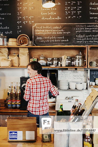 A woman working behind the counter in a coffee shop. Business owner.