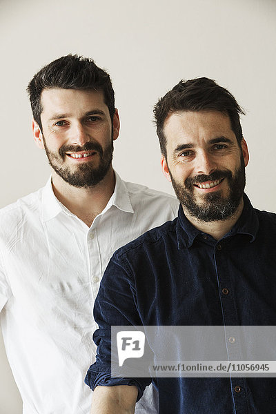 Porträt von zwei bärtigen Männern  die in die Kamera lächeln.