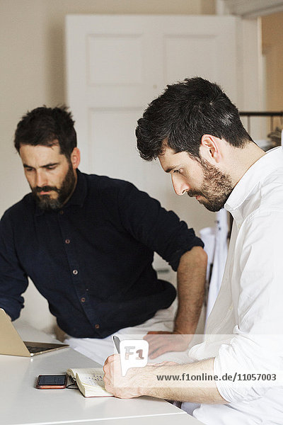 Two bearded men in a bakery  writing in a notebook and working on a laptop computer.
