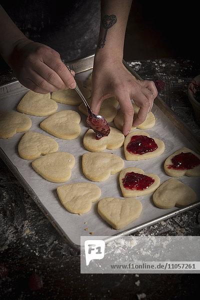 Valentinstag beim Backen  Frau streicht Himbeermarmelade auf herzförmige Kekse.