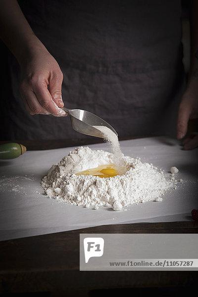 Valentine's Day baking  woman preparing dough for biscuits  adding sugar.