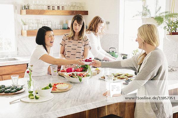 Four women in a kitchen preparing lunch.