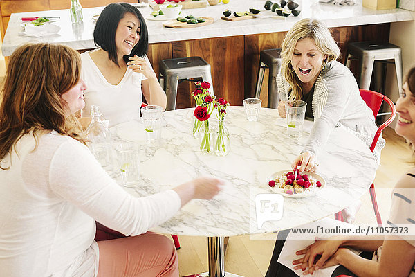 Four friends around a table having lunch together.