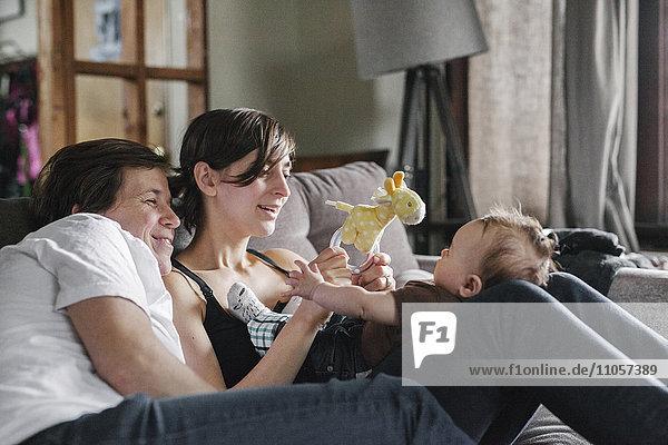Ein gleichgeschlechtliches Paar  zwei Frauen  die ihr 6 Monate altes kleines Mädchen ansehen.